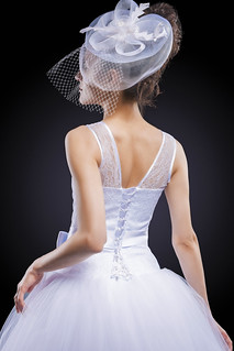 Wedding and Fashion Concept. Portrait of Young Caucasian Female Lady in Tailored Wedding Dress Made to Order Against Black