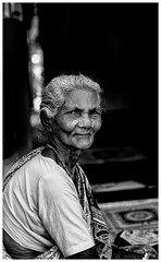 Portrait of an old woman in front of her home
