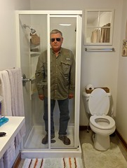 Man Wearing Sun Glasses in the Shower Stall of Cabin 1