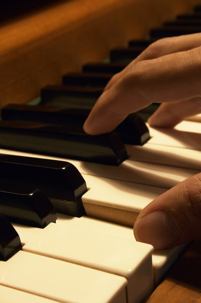 hand playing a piano keyboard