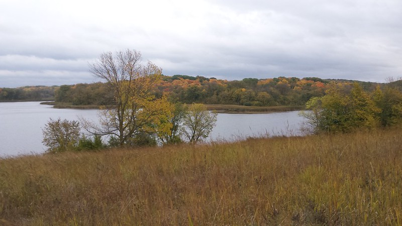 prairie in the foreground, a lake with a couple trees on the close side, and lots of colorful trees on the far side