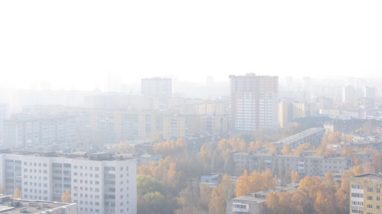 City view through dense smog on a sunny autumn day