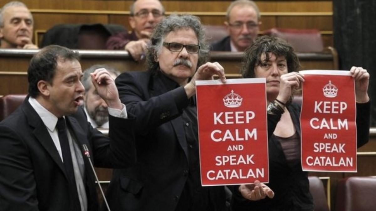 2012年加泰隆拿議員拿著寫著Keep Calm and Speak Catalan的海報,在議會內反對西班牙中央政府試圖干涉加泰隆拿身的教學語言。(網上圖片)