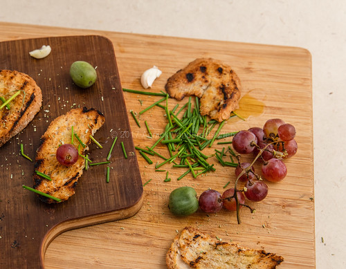 Grilled bread slices, grapes, chives, kiwi berries and garlic.