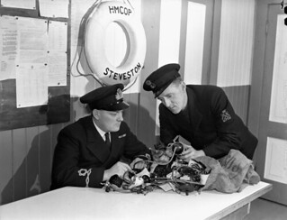 A Lieutenant of the Royal Canadian Navy Volunteer Reserve (RCNVR) and a Petty Officer of the Royal Canadian Navy examine engine parts removed from confiscated... fishing boats... / Lieutenant de la Réserve de volontaires de la Marine royale du Canada