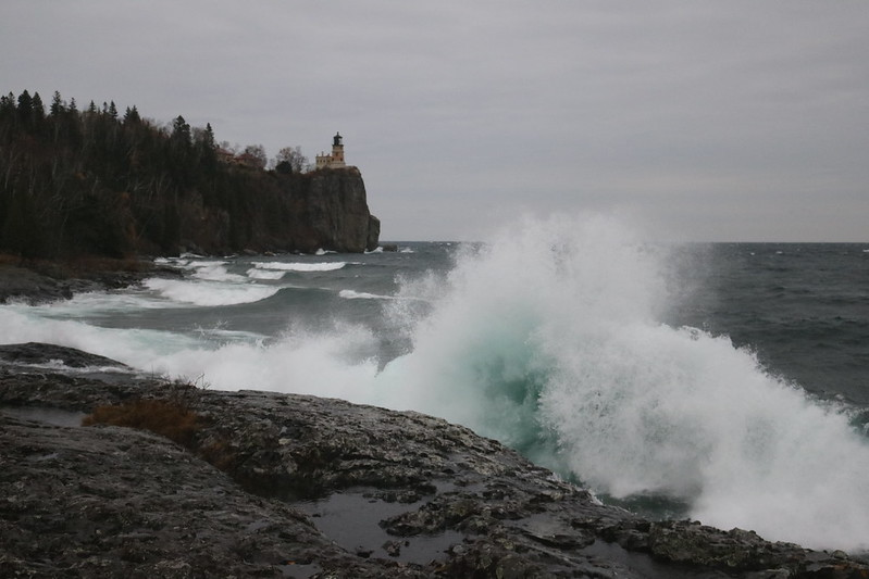 a wave just breaking, a large splash in the middle and extending downward toward the right, with several waves lining up down the shoreline in front of the lighthouse