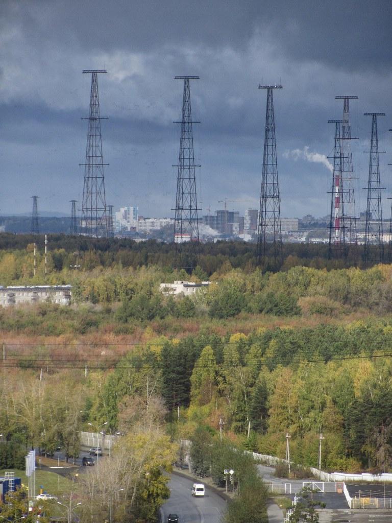 giant radio antennas behind autumn forest against dramatic sky