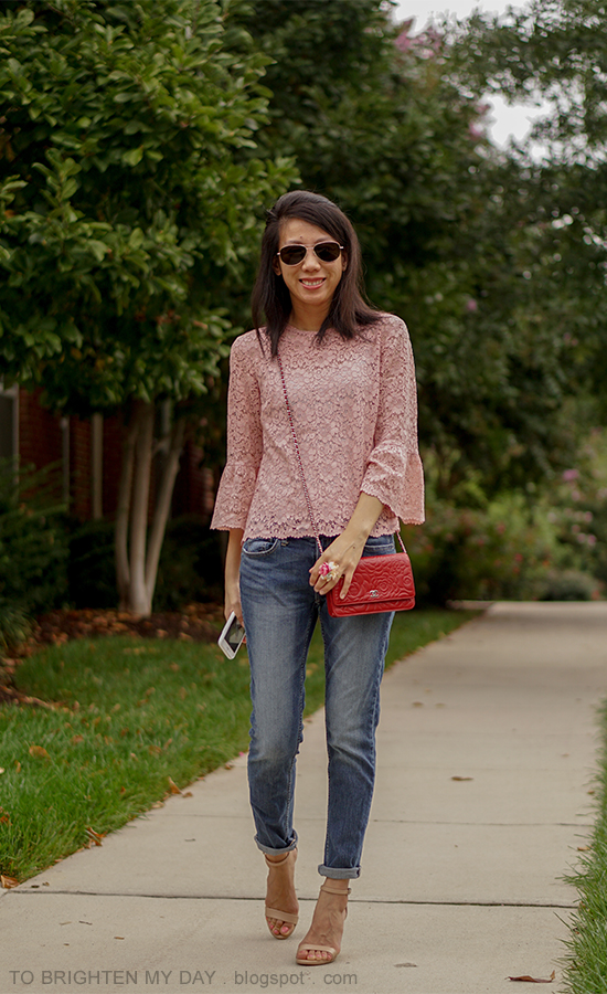 pink lace top with bell sleeves, floral ring, red embossed crossbody bag, girlfriend jeans, nude heels