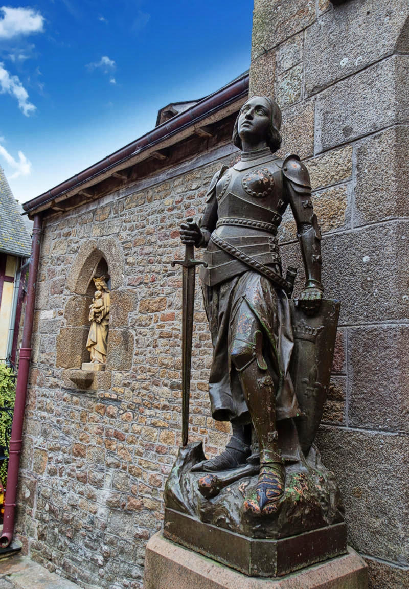 Statue of Joan of Arc next to the transept door of the Saint-Pierre church of Mont-Saint-Michel, Manche, France. Credit EdouardHue