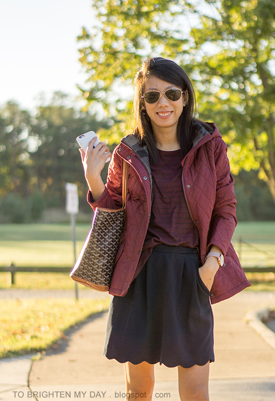 red quilted jacket, burgundy striped top, navy skirt with scallop hem, oversized watch, monogrammed tote