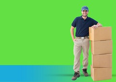 Confident delivery boy standing next to stacked boxes against green background