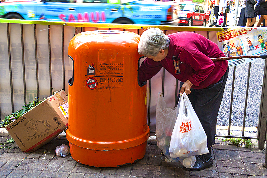 White haired woman with cane digging through trash can--Hong Kong
