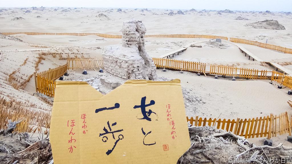 小僧落書き、背景はニヤ遺跡仏塔(撮影:筆者)