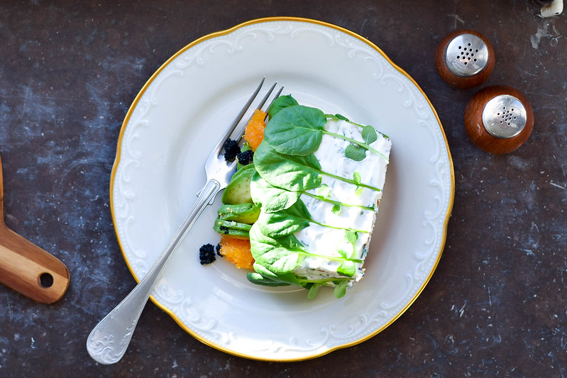 En bit vegansk smörgåstårta ligger på en vit sirlig tallrik med guldkand