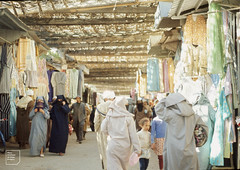 Fes. Garment stalls and ladies in yashmaks
