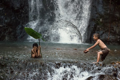 Rural children playing water with friend  in waterfall at countryside.Lifestyle of Asian rural children.