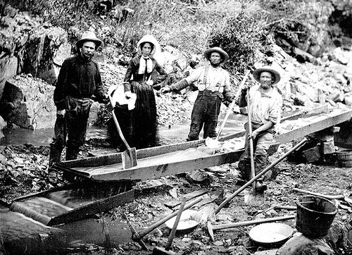 A woman with three men panning for gold during the California Gold Rush. Photo taken on July 9, 1850.