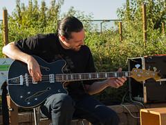 Bassist Stephen Coronado tuning up before his performance in the CapRadio Garden.
