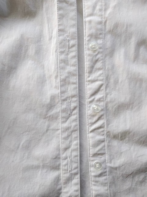 A set in button placket on a white button up shirt.