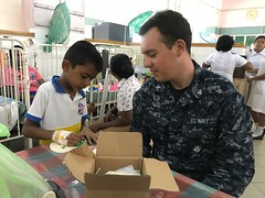 Information Systems Technician 3rd Class Joe Holmes does crafts with a boy at Lady Ridgeway Hospital during a volunteer event with Nimitz Carrier Strike Group, Oct 29.  (U.S. Navy/Lt. j.g. Michelle Tucker)