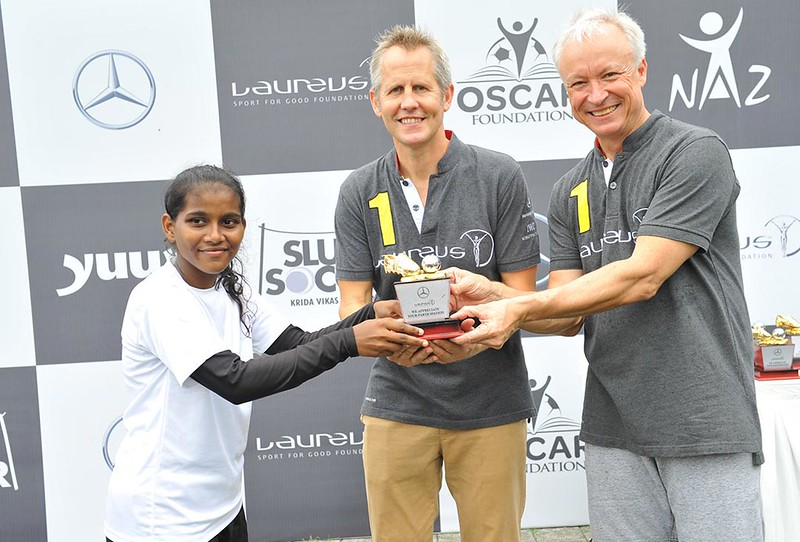 (R-L)-Roland-Folger---MD&CEO,-Mercedes-Benz-India-and-Andy-Griffiths,-Global-Director-at-Laureus-Sport-for-Good-presenting-trophy-to-a-young-girl-footballer