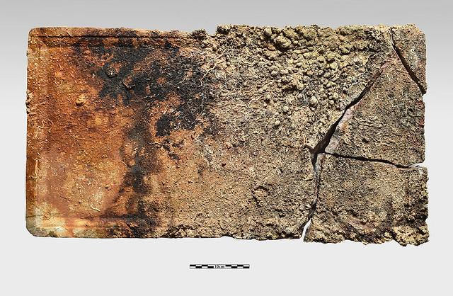 Ορθογώνια πρακτικώς ακέραιη πλάκα από πολύχρωμο ερυθρωπό μάρμαρο, από επίστεψη τράπεζας με περιχείλωμα στην κυρία όψη, διαστάσεων 68 εκ. x 35 εκ.  πάχους 5 εκ.