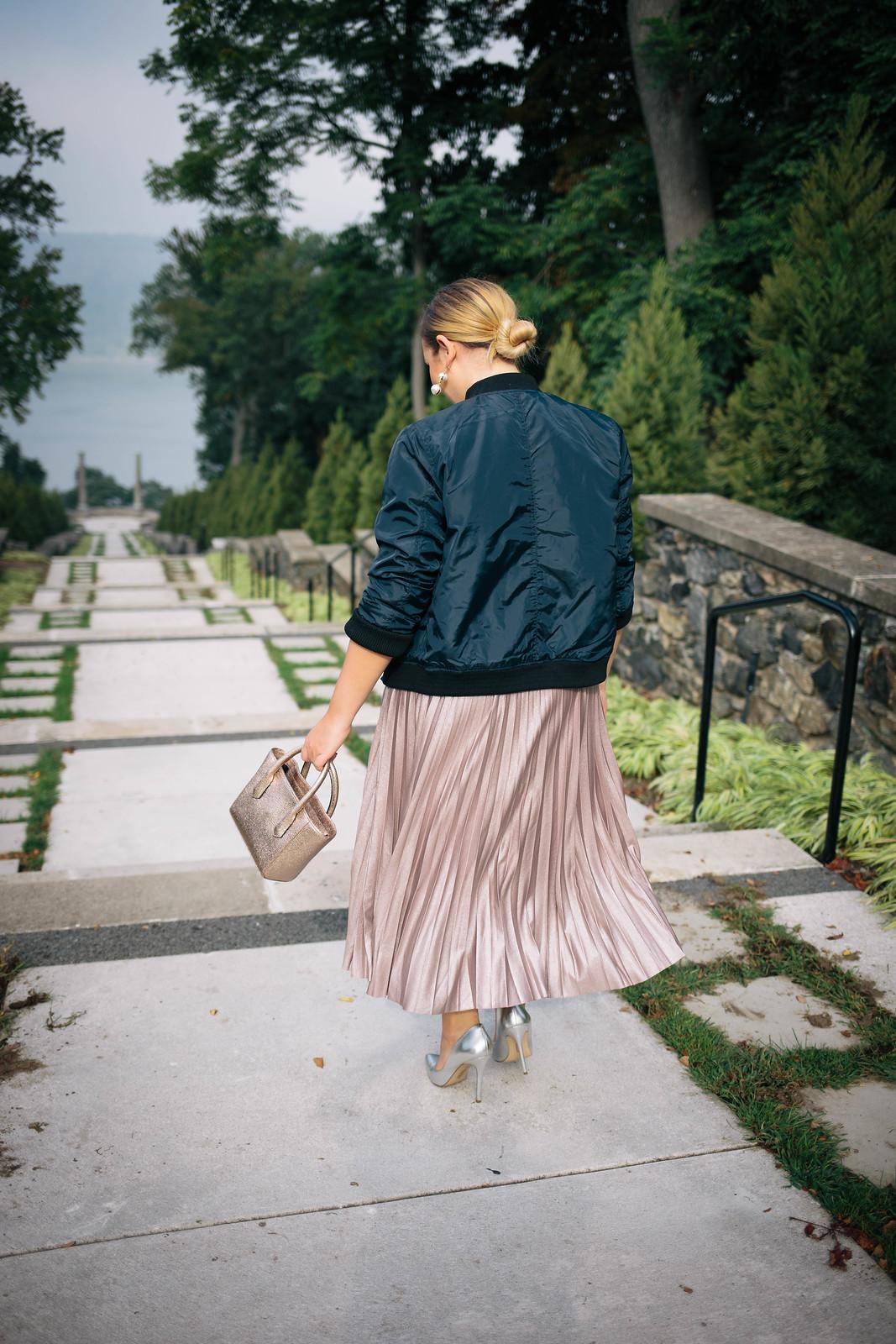 Navy Bomber Jacket Metallic Blush Pleated Midi Skirt Silver Heels Pearl Earrings Low Blonde Hair Bun Untermyer Park Yonkers NY