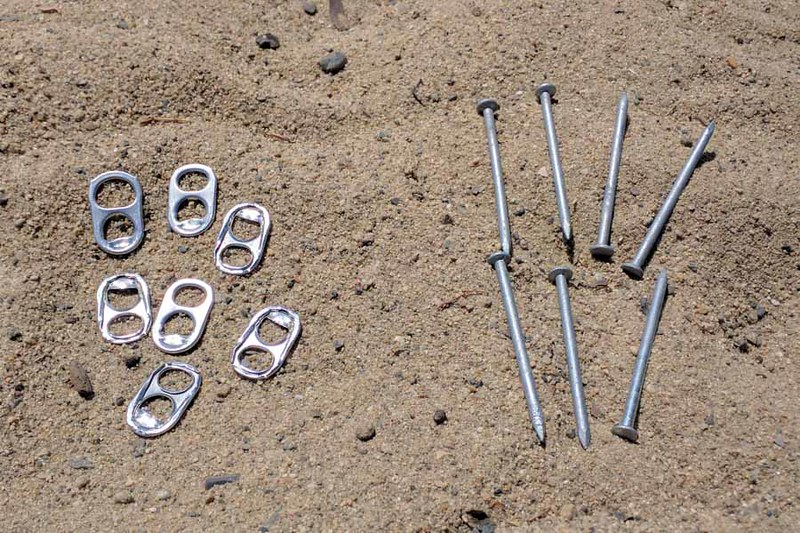 soda can pull tabs and nails on sand