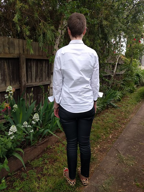 A woman stands against a garden fence. She wears a white button up shirt, black coated jeans and leopard print flats..
