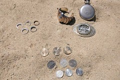 Metal treasures on the sand: coins, rings, jewelry, relics