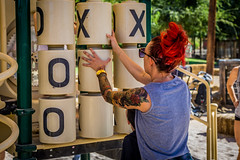 Mom with Bright Red Hair and Tattoos Playing a Game of Tic Tac Toe at a Park