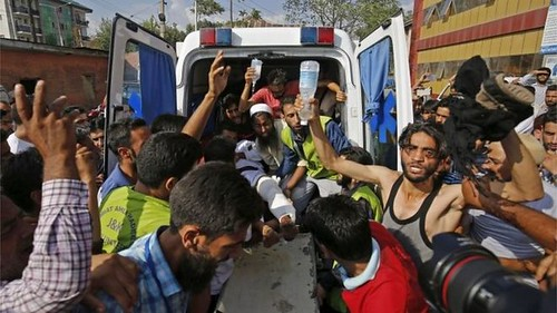 Volunteers carry an injured man from an ambulance outside a hospital who was shot during clashes