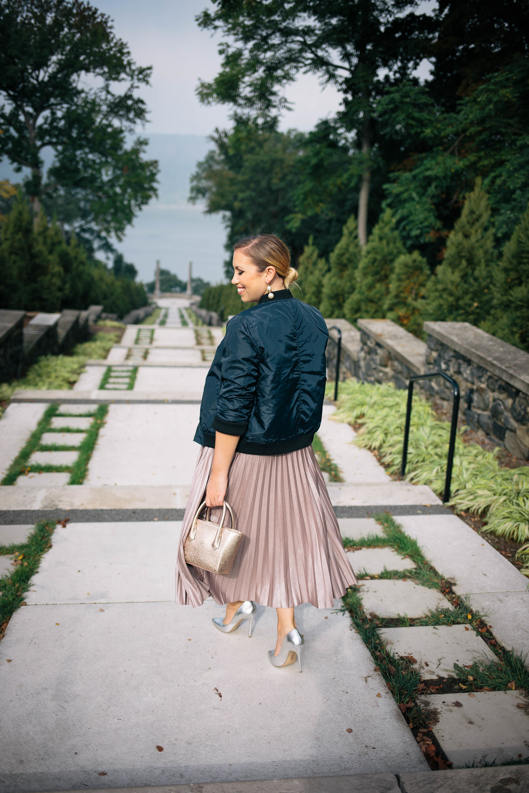 Navy Bomber Jacket Metallic Blush Pleated Midi Skirt Silver Heels Pearl Earrings Low Blonde Hair Bun Untermyer Park Yonkers NY