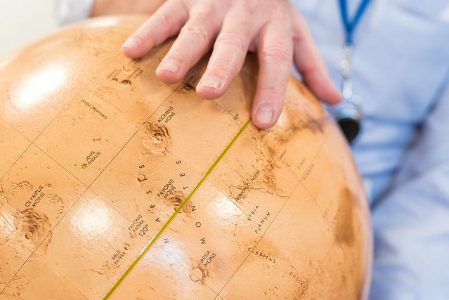Photo of a globe of Mars with Dr. Green's hand above.