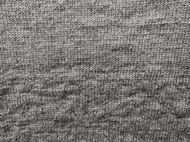 Hand knitted fabric, transitioning from smooth to lumpy.