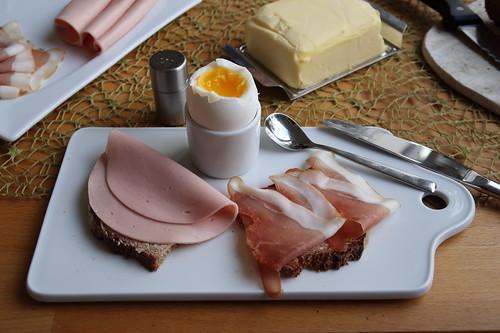 Fleischwurst und Schinkenspeck auf Holzofenbrot zum Frühstücksei
