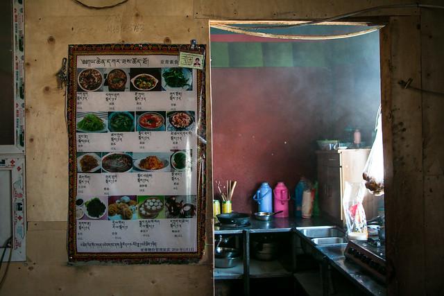 The restaurant wall with food menu and Kitchen, Yarchen Gar アチェンガルゴンパ 食堂の壁に掛かったメニューとその奥のキッチン