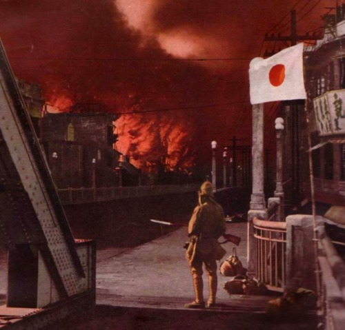 A Japanese soldier observes a city afire in China during Japan's occupation. Location unknown. 1938.