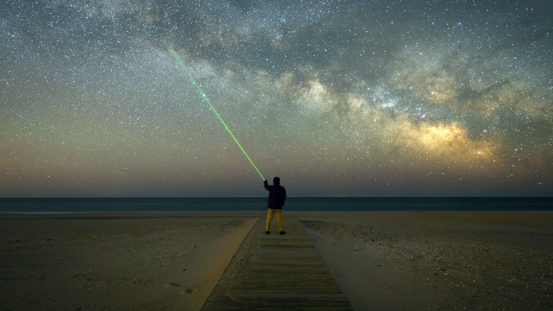 A man shines a laser pointer into the sky