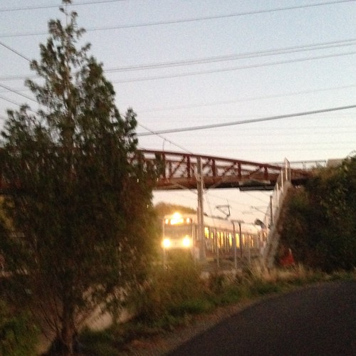 A northbound trolley passes under the Springwater Trail