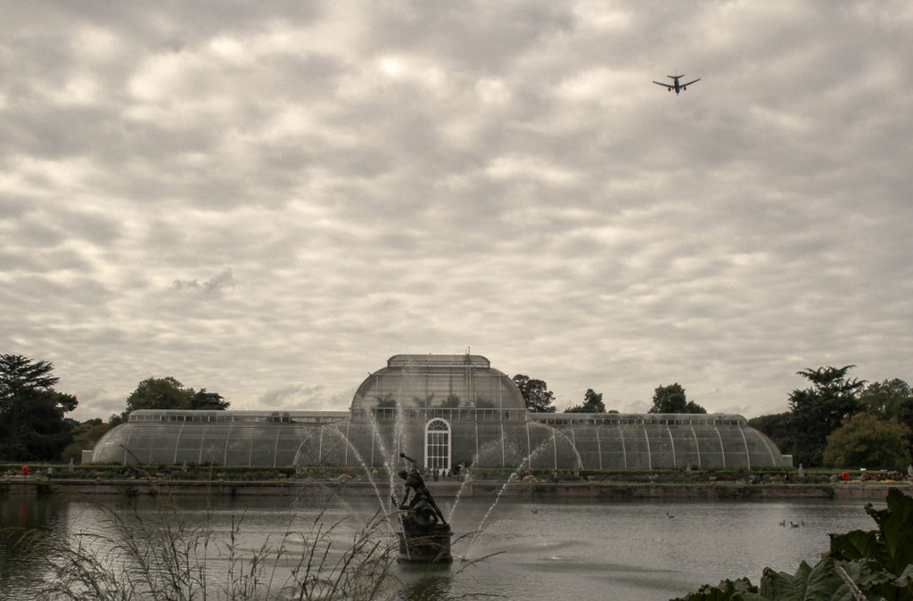 The Palm House at Kew Gardens, London, with the lake in front of it and a plane pasisng by ahead, preparing to land at Heathrow