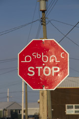 Octagon red stop sign with in Inuktitut (Syllabic), English and French snow on the ground
