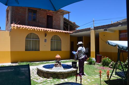 Die Wirten wäscht vor einem malerischen Brunnen im Innenhof des Hotels.