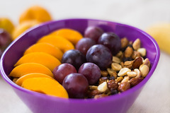 bowl of granola with grapes and peaches