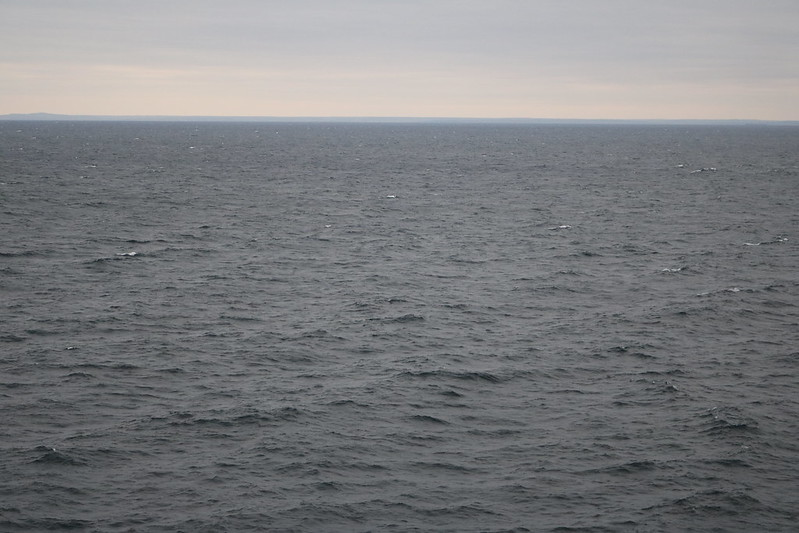 the horizon in the background, water with waves and small whitecaps in the bottom two-thirds