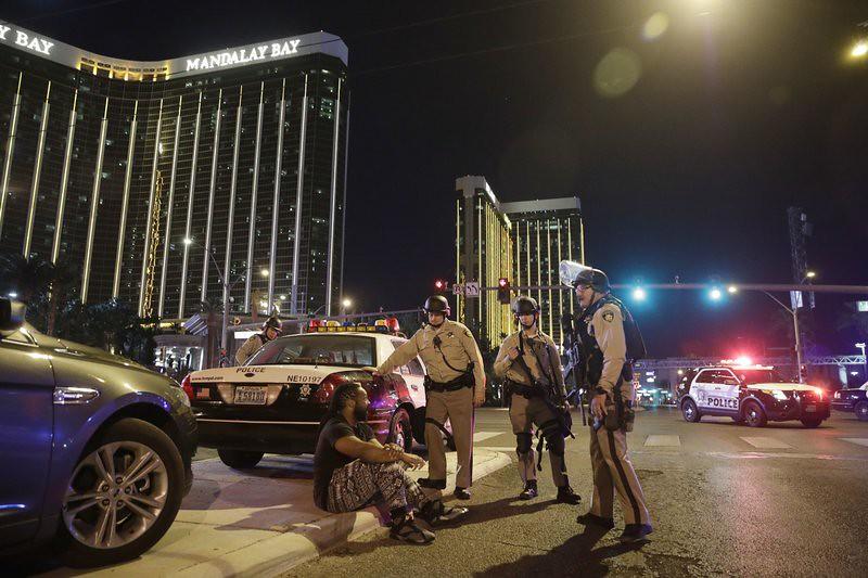 Petugas polisi berdiri di lokasi penembakan di dekat resor dan kasino Mandalay Bay di Las Vegas, Minggu, 1 Oktober 2017. Beberapa korban dibawa ke rumah sakit setelah syuting pada hari Minggu di sebuah festival musik di Las Vegas Strip. Foto: AP / John Locher