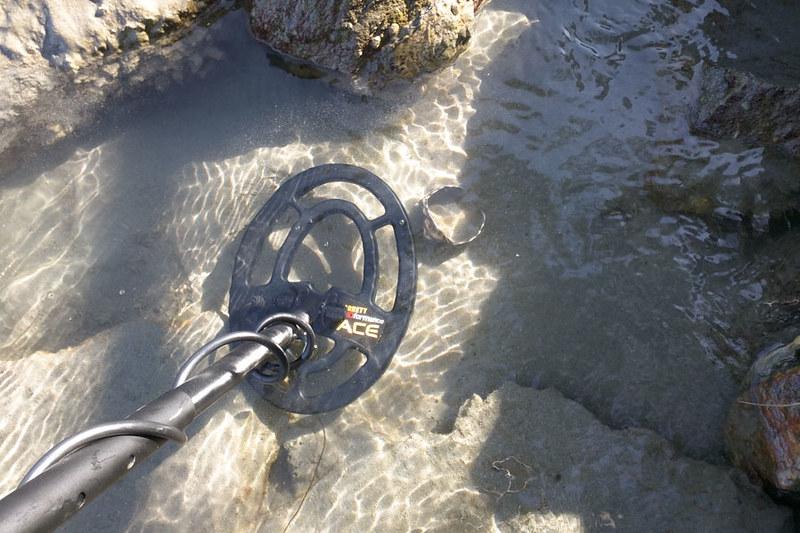 metal detector searching for treasure under water