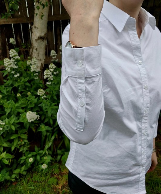 A woman stands against a garden fence. She shows the cuff of her white button up shirt.
