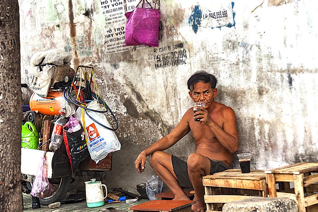 Shirless man on sidewalk--Saigon