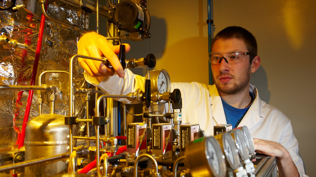 A student in a lab coat operates a piece of chemical engineering equipment